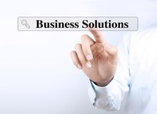 Business Solutions. Businessman is touching a search bar searching Business Solutions on a virtual screen with his finger Royalty Free Stock Images