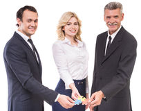 Business solutions. Businessmen and businesswoman joining jigsaw pieces of puzzle. Business strategy concept stock image