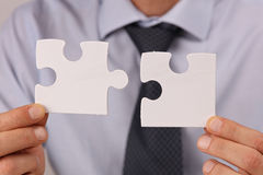 Business solutions, partnership concept. Businessman holding two pieces of a blank puzzle Royalty Free Stock Photos