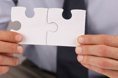 Business solutions, partnership concept. Businessman holding two pieces of a blank puzzle Royalty Free Stock Image