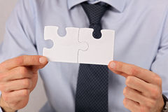 Business solutions, partnership concept. Businessman holding two pieces of a blank puzzle Royalty Free Stock Photography