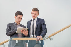 Business solutions. Two young and successful businessman standin. G on the stairs holding a laptop and smiling and looking into the camera in the meantime there Stock Images
