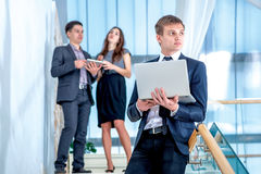 Business solutions.Young and successful businessman. Standing on the stairs holding a laptop and smiling and looking into the camera in the meantime there are Stock Images