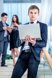 Business solutions.Young and successful businessman. Standing on the stairs holding a laptop and smiling and looking into the camera in the meantime there are Royalty Free Stock Photography