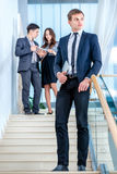 Business solutions.Young and successful businessman standing on. The stairs holding a laptop and smiling and looking into the camera in the meantime there are Stock Photos