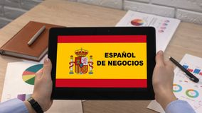 Business Spanish application against flag on tablet in female hands, tutorial stock video footage