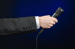 Business speech and topic: a man in a black suit holding a black microphone on a dark blue background in studio isolated Stock Images