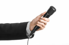 Business and speech topic: Man in black suit holding a black microphone isolated on white background in studio Stock Images