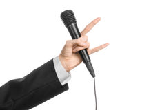 Business and speech topic: Man in black suit holding a black microphone isolated on white background in studio Stock Photos