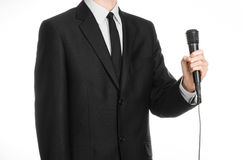Business and speech topic: Man in black suit holding a black microphone isolated on white background in studio Royalty Free Stock Image