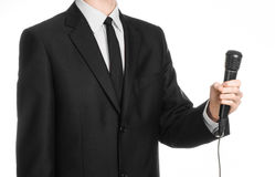 Business and speech topic: Man in black suit holding a black microphone isolated on white background in studio Royalty Free Stock Images