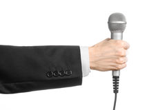 Business and speech topic: Man in black suit holding a gray microphone on an isolated white background in studio Stock Photography