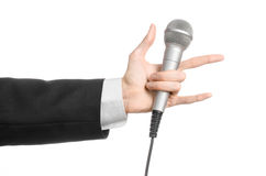 Business and speech topic: Man in black suit holding a gray microphone on an isolated white background in studio Royalty Free Stock Images