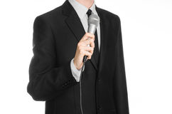 Business and speech topic: Man in black suit holding a gray microphone on an isolated white background in studio Royalty Free Stock Photo