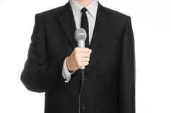 Business and speech topic: Man in black suit holding a gray microphone on an isolated white background in studio Royalty Free Stock Photos