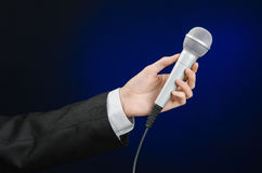 Business and speech topic: Man in black suit holding a microphone on a gray dark blue isolated background in studio Stock Image