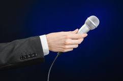 Business and speech topic: Man in black suit holding a microphone on a gray dark blue isolated background in studio Stock Photography