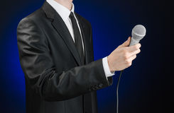 Business and speech topic: Man in black suit holding a microphone on a gray dark blue isolated background in studio Royalty Free Stock Images