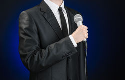 Business and speech topic: Man in black suit holding a microphone on a gray dark blue isolated background in studio Royalty Free Stock Photos