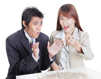 Business spilling the beans. Young Asian business team at a desk illustrating the English idiom and metaphor of spilling the beans for betraying a secret or Royalty Free Stock Images