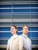 Business stand. Business man and woman stand together in front of modern building Stock Photography