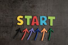 Business start begin the journey concept, colorful arrows point. Up to word START on blackboard cement wall to emphasize the important of initiation thinking royalty free stock images