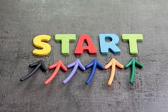 Business start begin the journey concept, colorful arrows point up to word START on blackboard cement wall to emphasize the stock photos