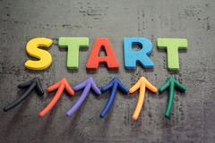 Business start or begin new life journey concept, colorful arrows point up to word START on blackboard cement wall. To emphasize the important of initiation stock photo