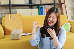 Business start up asian woman is happy with her online order from smartphone . royalty free stock photography