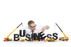 Business start up: Businessman building business-word. Stock Photos
