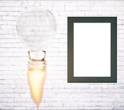 Business startup concept blank frame. Business start up idea concept with abstract rocket fire lightbulb and blank picture frame on white brick wall background Stock Image