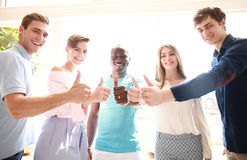 Business, startup and office concept - happy creative team showing thumbs up in office. Stock Images