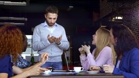 Business, startup and people concept - happy creative team with computers and folder discussing project in loft shared. Space stock footage