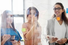 Businesswomen with pie chart on office glass board Stock Images