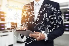 Business, startup, presentation, strategy and people concept. Business man in suit with startup diagram sketch popup from tablet with light effect Stock Photo