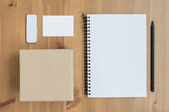 Business stationary set. On wooden background, top view (Box, open empty notebook, pencil, card, flash Royalty Free Stock Photography