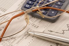 Business still-life. With financian newspaper, pen, glasses and calculator Royalty Free Stock Image