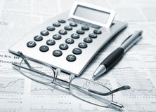 Business still life. Calculator, pen and glasses lie on the newspaper Stock Photos