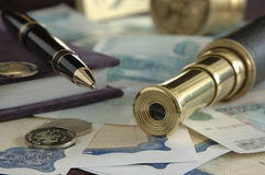 Business still-life. Still life of a ballpoint pen, a telescope and coins Stock Images