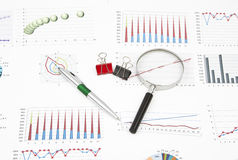 Business still-life diagrams, magnifier, pen, paperclip Royalty Free Stock Images