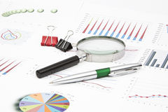 Business still-life diagrams, magnifier, pen, paperclip Royalty Free Stock Photography