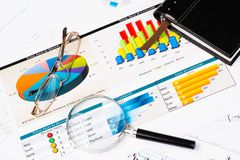 Business still life. Diary, glasses, magnifying glass, and business documents with charts, business still life Stock Photo