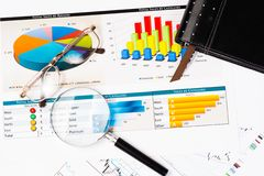 Business still life. Diary, glasses, magnifying glass, and business documents with charts, business still life Royalty Free Stock Photos