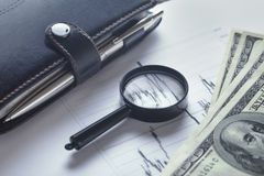 Business still-life with a magnifying glass, diary and bills Royalty Free Stock Photos