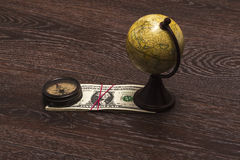 Business still-life traveler. Compass, Globe, money on a wooden background Royalty Free Stock Photo