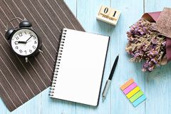 Desk table with open notebook paper, cube calendar and clock Royalty Free Stock Image