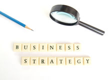 Business strategy concept. A conceptual photograph of the words business strategy, spelt out in blocks, taken on clean white background with magnifying glass and Royalty Free Stock Photo