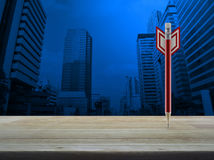 Business strategy concept. Red pencil in the shape of a dart on wooden table over modern office city tower, Business strategy concept Stock Photo
