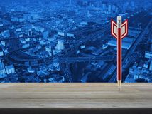 Business strategy concept. Red pencil in the shape of a dart on wooden table over modern office city tower background, Business strategy concept Royalty Free Stock Photography