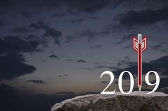 Business strategy happy new year 2019 concept. Red pencil in the shape of a dart arrow with 2019 white text on rock mountain over sunset sky, Business strategy stock illustration
